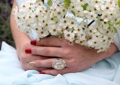 Woman in wedding dress holding flowers and wearing beautiful ring by Aramaya