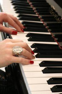 Woman playing piano, wearing beautiful Aramaya ivory ring